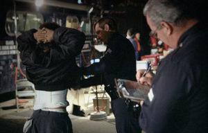 Suspected drug dealer being processed by police